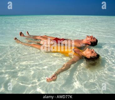 Pareja joven relajante en aguas poco profundas, playa, Maldivas, Océano Índico