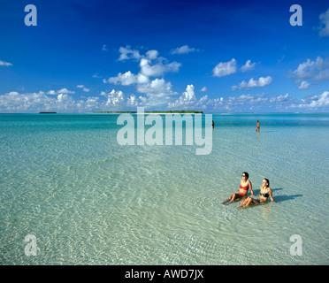 Las mujeres jóvenes de relax en aguas poco profundas, en la parte posterior de la isla, Maldivas, Océano Índico