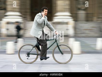 Hombre vestido con traje, la celebración de teléfono celular a la oreja y andar en bicicleta, borrosa.