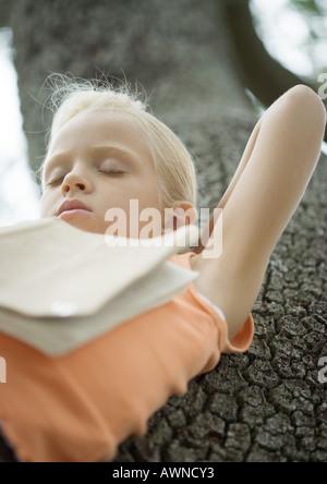 Chica en el árbol durmiendo con el libro en el pecho