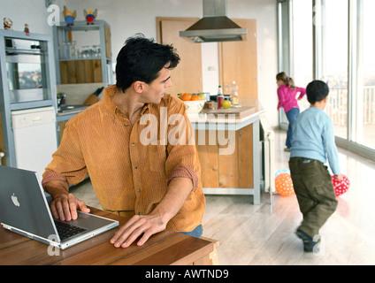 Padre mirando atrás a niños jugando con pelotas en la casa.