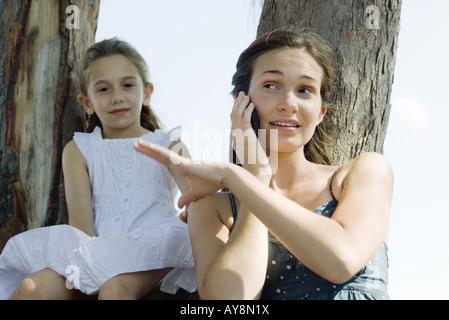 Mujer joven con teléfono celular, hermana pequeña de la mano de cepillado fuera de su hombro