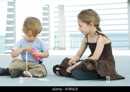 Chico sentado en el suelo globo inflado con bomba de aire, hermana mayor viendo