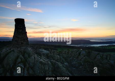 Cairn trig punto en la parte superior de 'cómo' Gummers al amanecer, Lake District, Cumbria, Inglaterra.