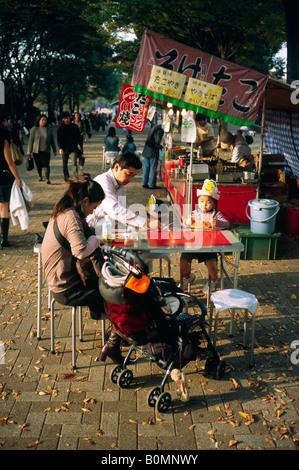 Joven familia disfrutar de una cena al aire libre en el parque Yoyogi en la capital japonesa de Tokio.