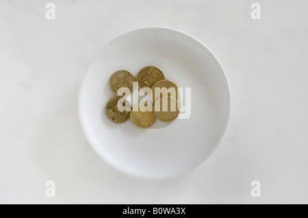 Las monedas de euro en una placa blanca sobre una superficie de mármol, el pago por el uso del inodoro