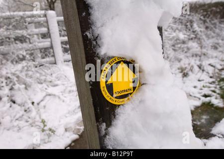 Caminata invernal: Un poste cubierto de nieve y una valla de ferrocarril con un letrero amarillo en Sussex.