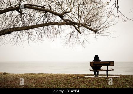 Mujer sentada en un banco al lado del lago Taupo, Nueva Zelanda. Capó levantado contra el frío invernal
