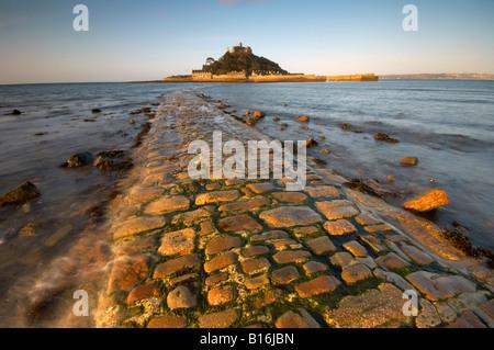 Olas corriendo por la antigua calzada de piedra conduce a St Michaels Mount al amanecer Marazion Cornwall UK