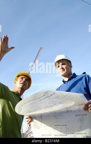 Ángulo de visión baja de dos arquitectos masculinos en sitio en construcción