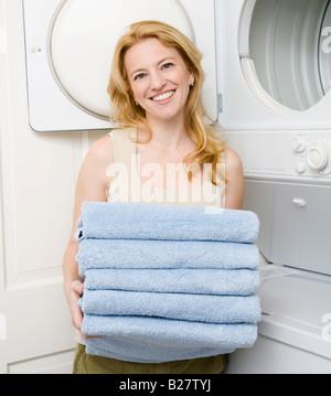 Mujer sosteniendo toallas plegadas