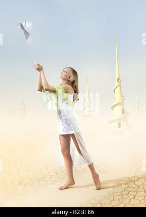 Hermosa joven, liberando una blanca paloma de paz hechas de papel en el cielo azul en un desierto extraterrestre mundo cubiertas