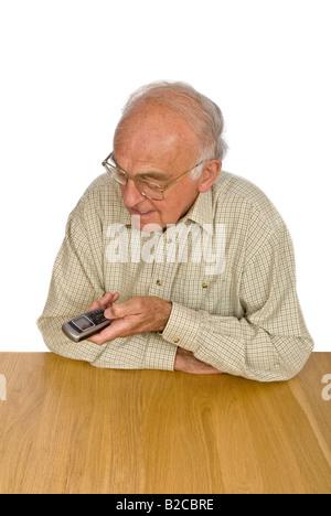 Vertical de un anciano caballero tiene dificultad para ver y utilizar los botones pequeños en un teléfono móvil.
