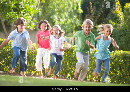 Cinco jóvenes amigos corriendo en exteriores sonriendo