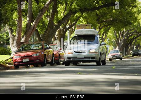 Chevy Aveo bajando la calle arbolada con colchón y cajas en el techo