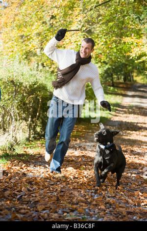 El hombre exterior con el perro en la ruta en el parque sucursal sonriendo (enfoque selectivo) Foto de stock