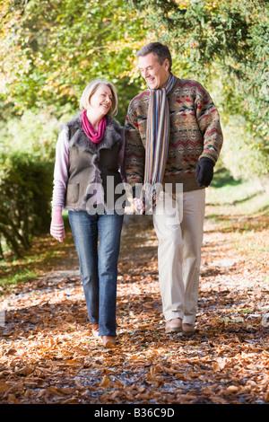 Par afuera caminando en el camino en el parque tomados de la mano y sonriendo (enfoque selectivo)