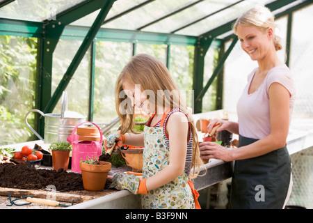 Niña y mujer en invernadero poner suelo en potes sonriendo
