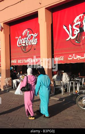 Dos mujeres veladas delante del anuncio de coca-cola en árabe en la Plaza Djemma el-Fna, la plaza 'impostor' o 'plaza del ahorcado' Foto de stock