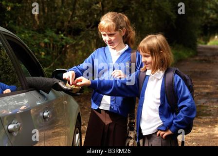 Las niñas solas en un carril del país tomar dulces de un extraño conduciendo un coche