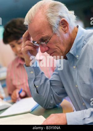 Hombre sentado cerca de la mujer en biblioteca con libros y cuadernos (enfoque selectivo)
