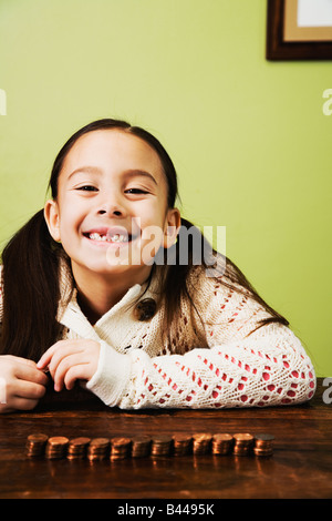Chica asiática junto a monedas apiladas