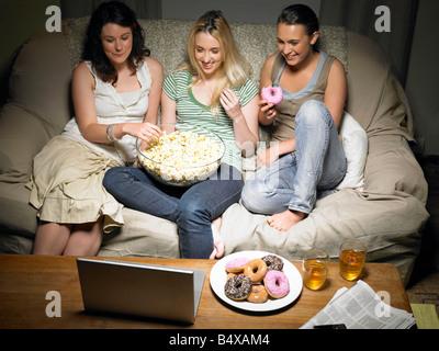 Tres jóvenes mujeres viendo la película Foto de stock