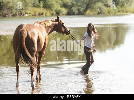 Adolescente paseos a caballo a través de un río superficial.