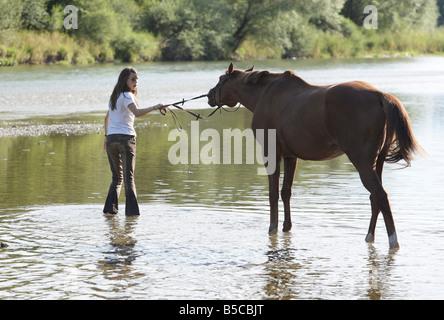 Adolescente paseos a caballo a través de un río superficial