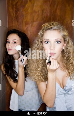 Chicas haciendo el maquillaje en el baño. Foto de stock