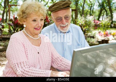 Feliz pareja senior sobre su ordenador portátil en un hermoso escenario al aire libre