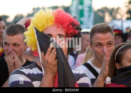 Ventilador con una peluca con los colores de la bandera alemana viendo el juego final de la EM en el fútbol la milla de los fans de Berlín, Berlín