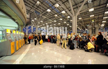 Pasajeros que esperan en las colas en los mostradores de facturación, el aeropuerto de Stuttgart, Baden-Wurtemberg