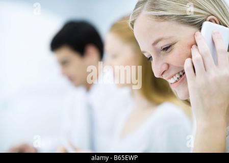 Profesional joven mujer hablando por teléfono celular, los colegas que trabajan en segundo plano.