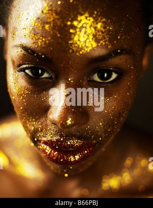 Mujer joven cubierto con hojas de oro Foto de stock