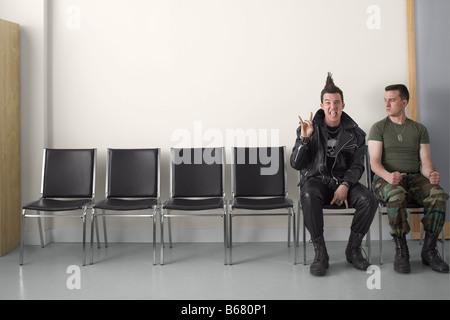 Punk y soldado en zona de espera Foto de stock
