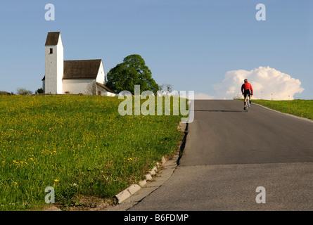 Los ciclistas de carreras de caballo en una carretera pasado una iglesia, Steinkirchen, Chiemgau, Baviera, Alemania, Europa