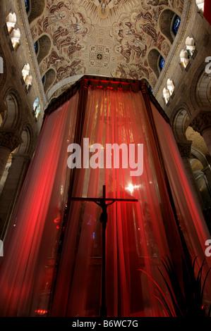 Una estatua de Jesús en la cruz siluetas contra una cortina roja en la iglesia.