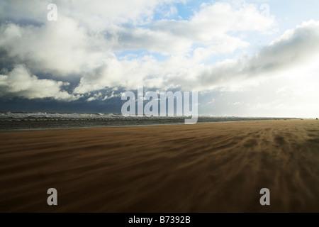 Día de invierno en la costa, nubarrones que se aproxima, el viento azuzando la arena. Fotografía de paisaje de Lincolnshire. Playa