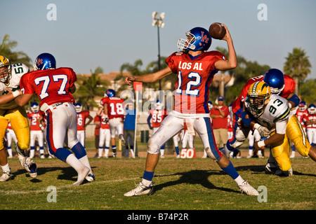 Un jugador lanzando el balón en un partido de fútbol americano con futbolistas corriendo alrededor, Huntington Beach, California, EE.UU.
