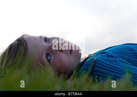 Headshot, ocho años de edad, niña acostada en la hierba mirando hacia arriba, Winnipeg, Canadá