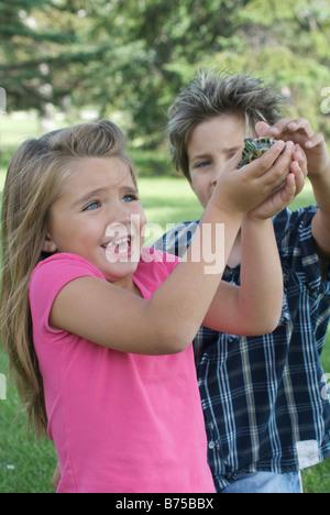 Niño de 8 años y niña de seis años con la tortuga, Winnipeg, Canadá Foto de stock