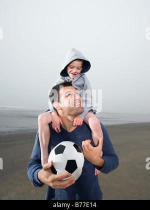 Hijo de padre llevar sobre los hombros y sosteniendo un balón de fútbol en la playa