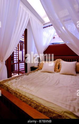 Cama con dosel con cortinas blancas atadas en las esquinas