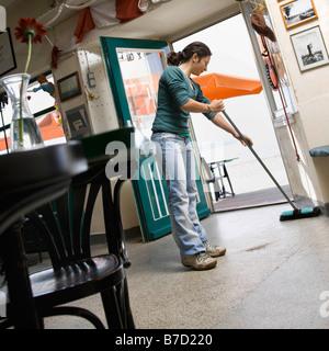 Mujer barriendo en un café