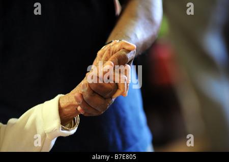 Un cierre de ancianos sij manos señoras como ella ayudó a su silla en un hogar de atención extra multicultural Bradford, Foto de stock