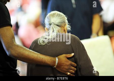 Una anciana señora sij es ayudado a su silla en un hogar de atención extra multicultural Bradford, West Yorkshire Foto de stock