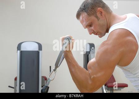 Hombre haciendo el brazo rizos con mancuernas Foto de stock