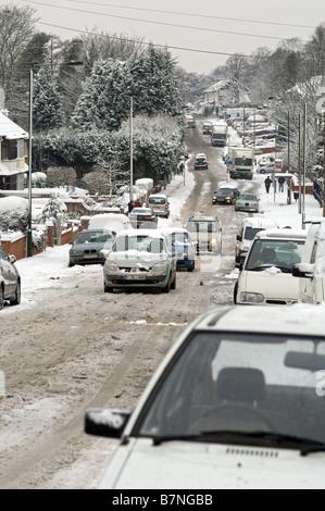 Tráfico en la nieve en la colina, calle no gritted