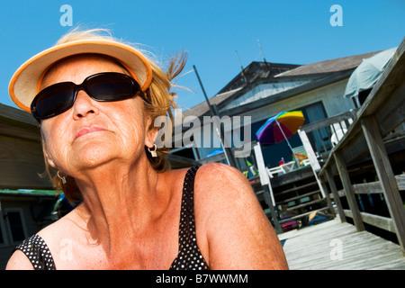 Mujer sentada en las escaleras en Beach House obteniendo un bronceado Foto de stock